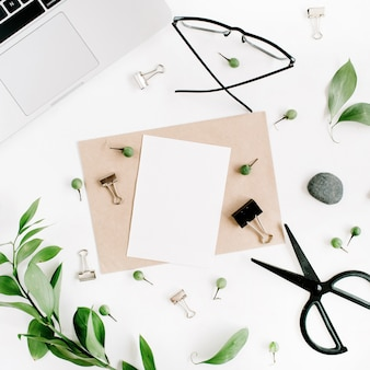 White office desk workspace with paper blank and green leaves