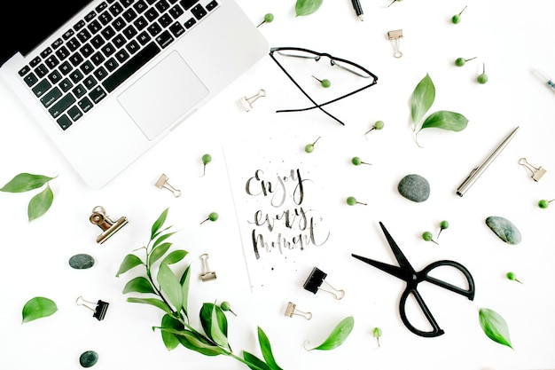 White office desk workspace with quote enjoy every moment, green leaves and office supplies