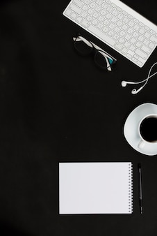 White office supplies and coffee cup on black desktop