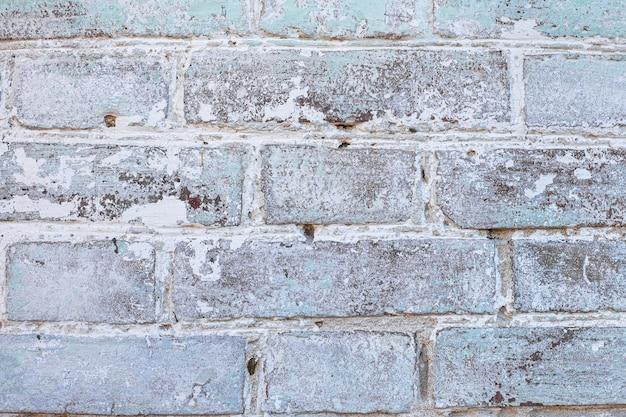 Белая старая кирпичная стена с предпосылкой краски шелушения, текстурой, местом для текста.