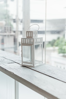White old lamp on white painted wooden table with glass window and trees in background.
