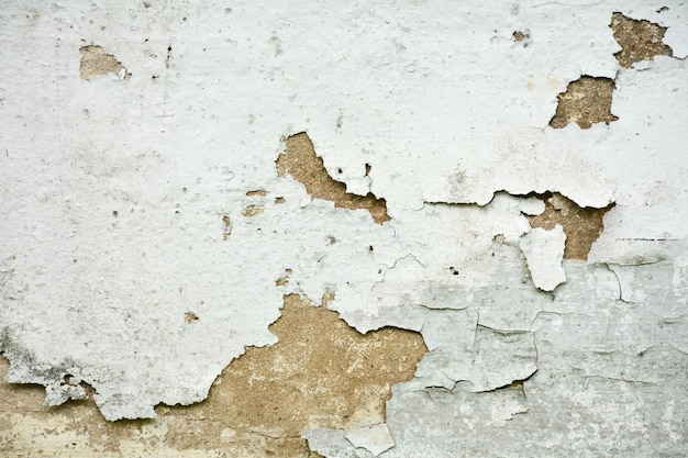 The white old paint texture is chipping and cracked at the wall