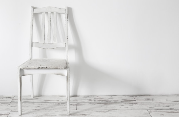 Белый старый деревянный стул в белом винтажном интерьере