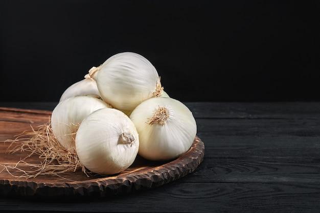 Белый лук на деревянной доске на черном столе. органическая еда