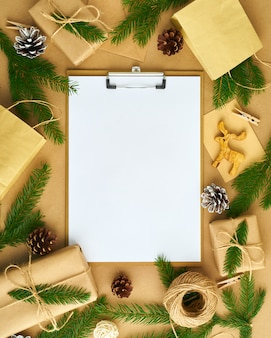 White open blank on clipboard and christmas decoration lying on beige craft paper