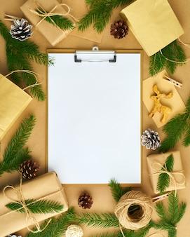 クリップボードとベージュのクラフトペーパーの上に横たわるクリスマスの装飾に白いオープン空白