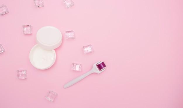 Белая открытая банка со сливками, мезороллером и кубиками льда