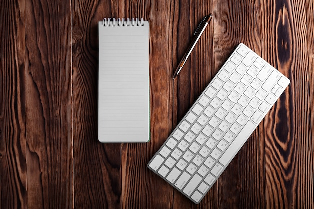 The white open notepad and computer keypad isolated on the wooden desktop