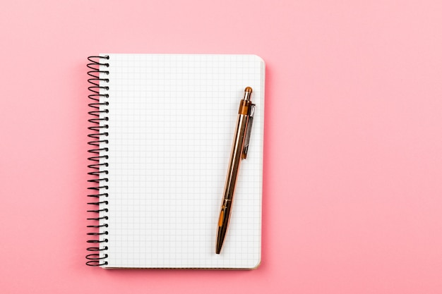 The white open notepad isolated on the pink background