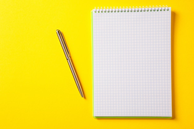 The white open notepad on silver pen isolated on yellow