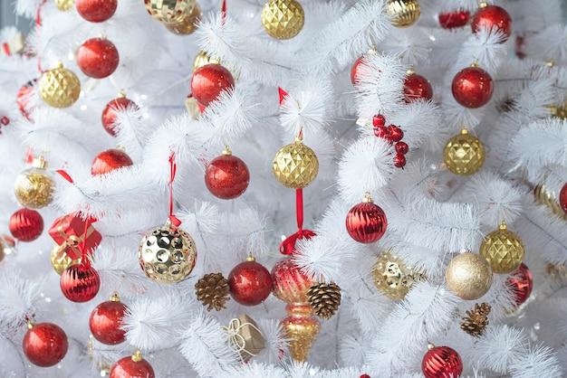 빨간색, 금색 장난감, 새해 구성이있는 흰색 또는 은색 크리스마스 트리