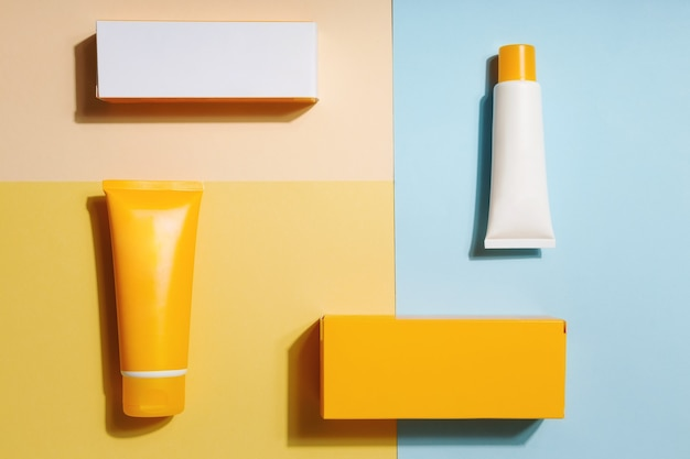 White and orange tubes and boxes of sunscreen on yellow and blue background sun protection