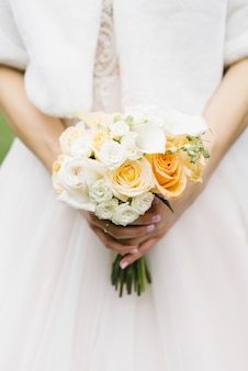 White and orange wedding bouquet in the hands of the bride