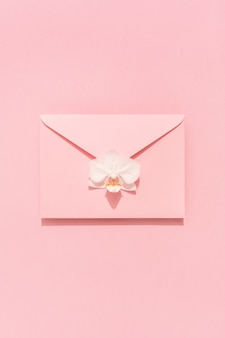 ピンクの封筒に白い蘭の花。おめでとうカード、女性、母の日、バレンタイン、誕生日。休日の背景。