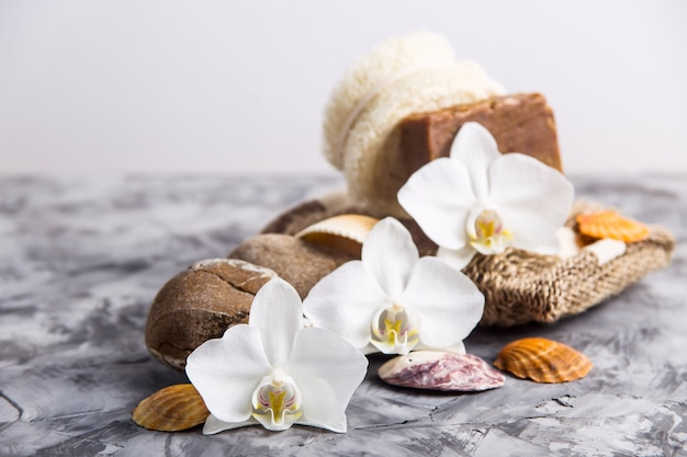 White orchid flowers next to sea stones and shells on a gray background