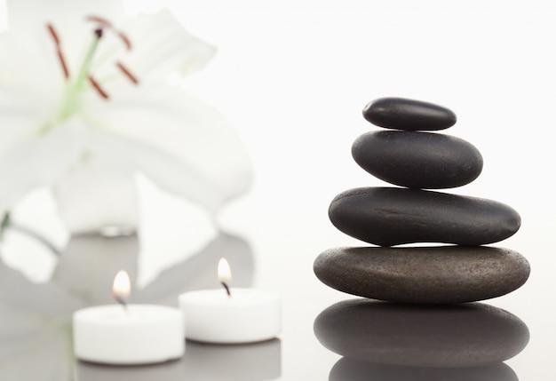 白い蘭、白い蝋燭と黒い小石の積み重ね
