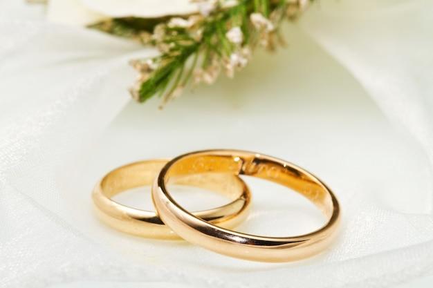 백색 난초와 백색 표면에 결혼 반지