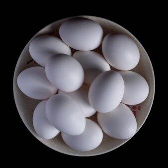 黒い食べ物の皿に置かれた白い有機鶏の卵