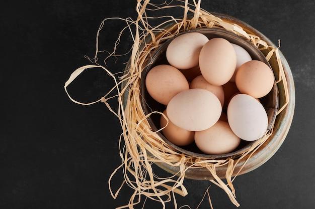 金属製のカップに白い有機卵、上面図。