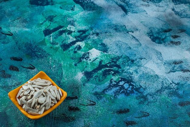 青いテーブルの上に、ボウルに白い有機ヒマワリの種。