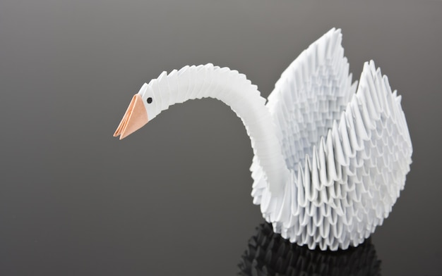 Белый лебедь оригами на серой поверхности. вид крупным планом
