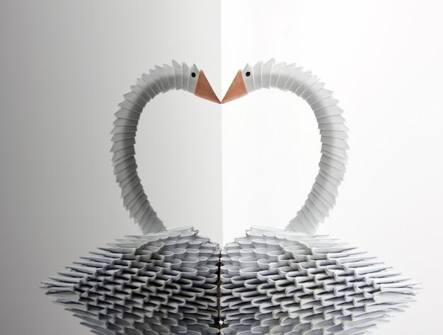 Белый лебедь оригами с отражением на серой поверхности
