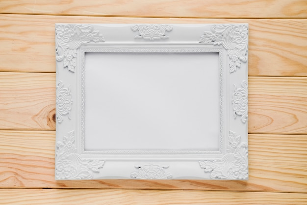 White ornamental frame with wooden background