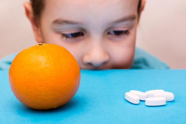 Белые овальные таблетки и спелый апельсин лежат перед лицом ребенка на синем фоне. лекарства и синтетические витамины. концепция выбора лекарств и натуральных фруктов. лечение для детей.
