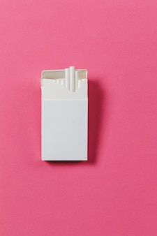 White pack of cigarettes on pink rose background