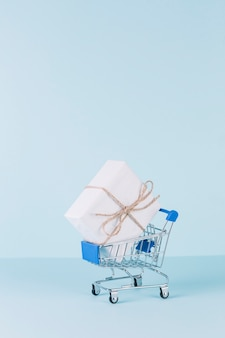 White package in shopping cart on blue background