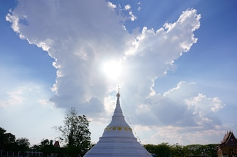 White pagoda is the backdrop in the sky with beautiful clouds.