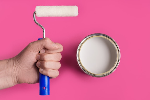 White paint can with paint roller on pink background.