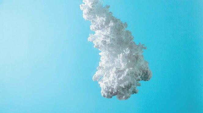 White paint cloud splash underwater against sky blue.