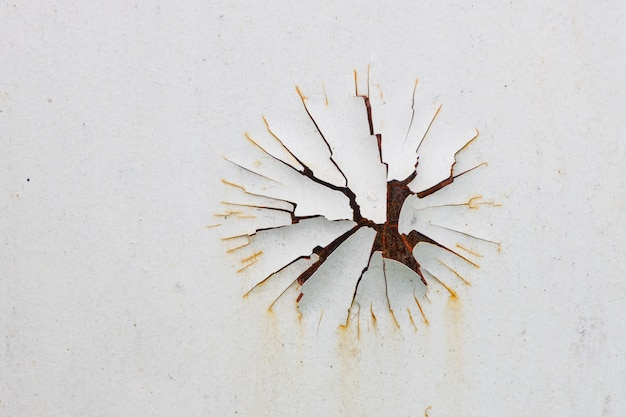 White paint peels off a rusty metal surface