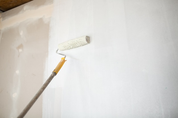 White paint roller in hand with drywall wall