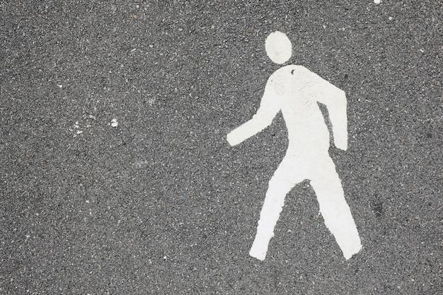 White painted man over black asphalt surface