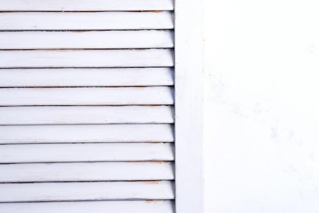 Белые окрашенные старые деревянные ставни и часть стены