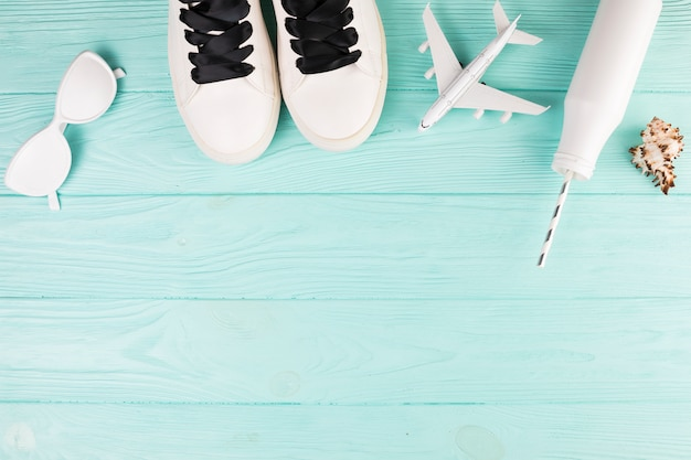 White painted shoes with toy plane and bottle with straw