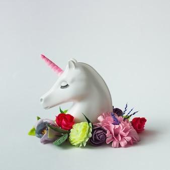 明るい白い表面に色とりどりの花と葉を持つ白い塗られたユニコーンの頭