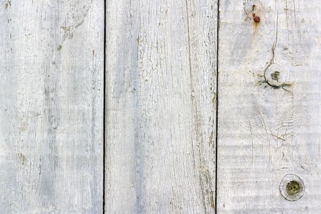 Покрашенная белизной выдержанная старая текстура деревянных доск с крупным планом потертостей и трещин. абстрактный деревянный фон