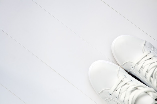 White pair of sport sneakers-new white tennis shoes on white background with copy space