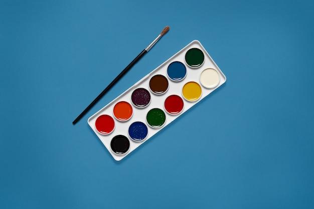 Белая палитра с двенадцатью различными цветами, находящимися в центре рисунка, без конуса, черная кисть, лежащая рядом с красками. призрачный синий цвет. художественная концепция. оборудование, необходимое для покраски.