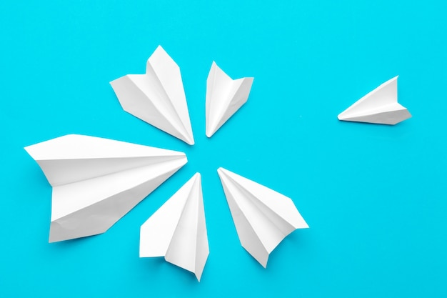 White paper airplane on a blue