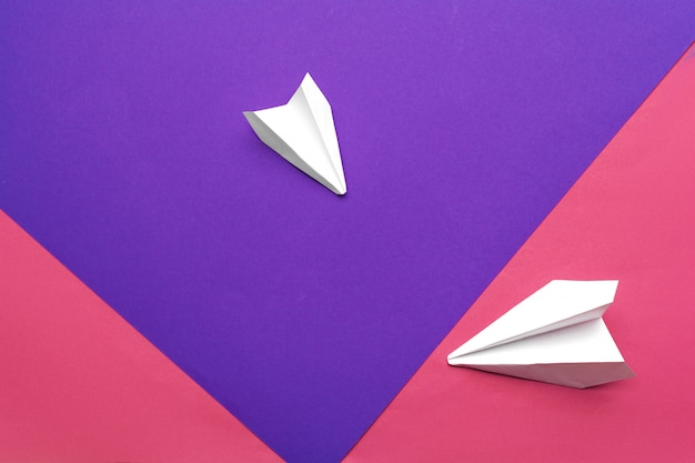 White paper airplane on a color block paper