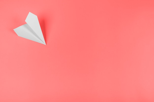 White paper airplane on the corner of the coral background