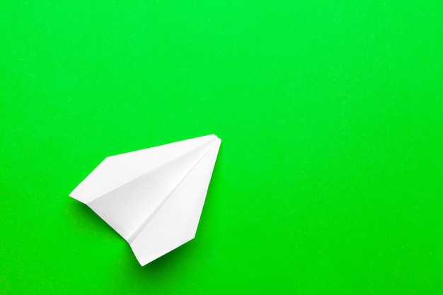 White paper airplane on a green paper