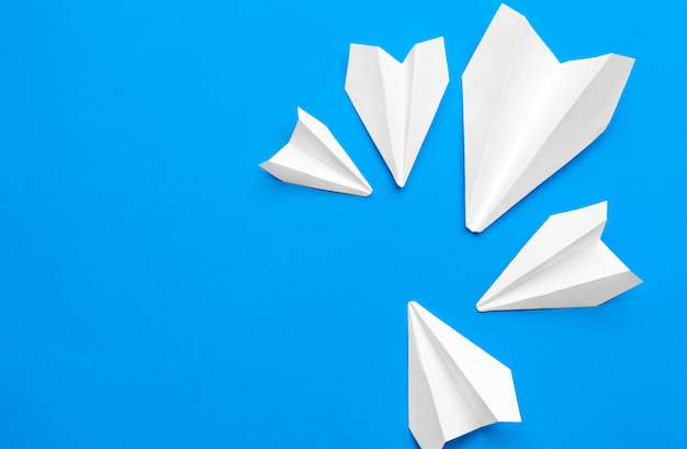 White paper airplane on a navy paper background