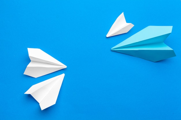 White paper airplane on a navy paper