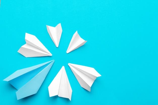 Белый бумажный самолетик на синем