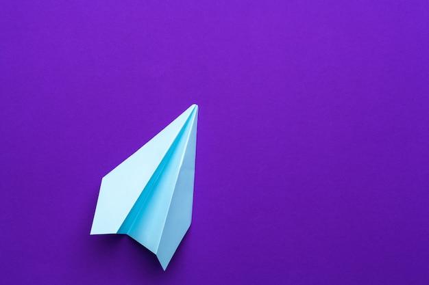 Белый бумажный самолетик на фиолетовом